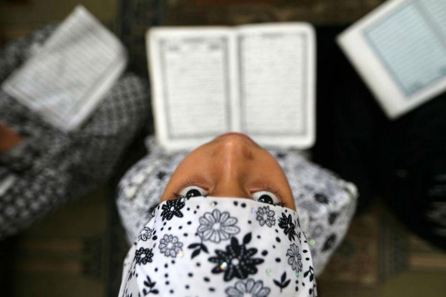دختری در حال خواندن قرآن در مسجدی در نوار غزه در منطقه RAFAH عکاس: Ibraheem Abu Mustafa مکان: RAFAH، فلسطین