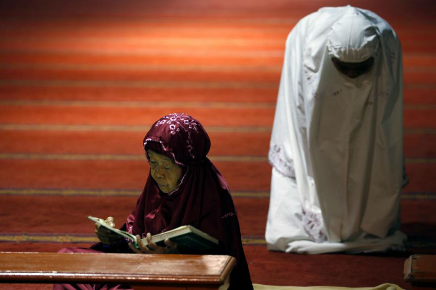 زن مسلمان در حال خواندن قرآن در روز اول ماه رمضان در مسجد استقبال در جاکارتا عکاس: Beawiharta Beawiharta مکان: جاکارتا، اندونزی