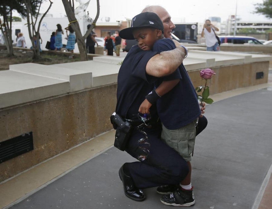 A Dallas Police officer hugs a child who came to pay respects at a makeshift memorial at Dallas Police Headquarters following the multiple police shootings in Dallas. REUTERS/Carlo Allegri