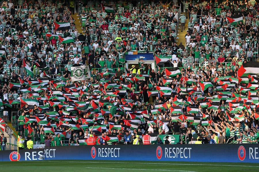 Fans hold up Palestine flags Action Images via Reuters / Russell Cheyne Livepic EDITORIAL USE ONLY. - RTX2LL5T