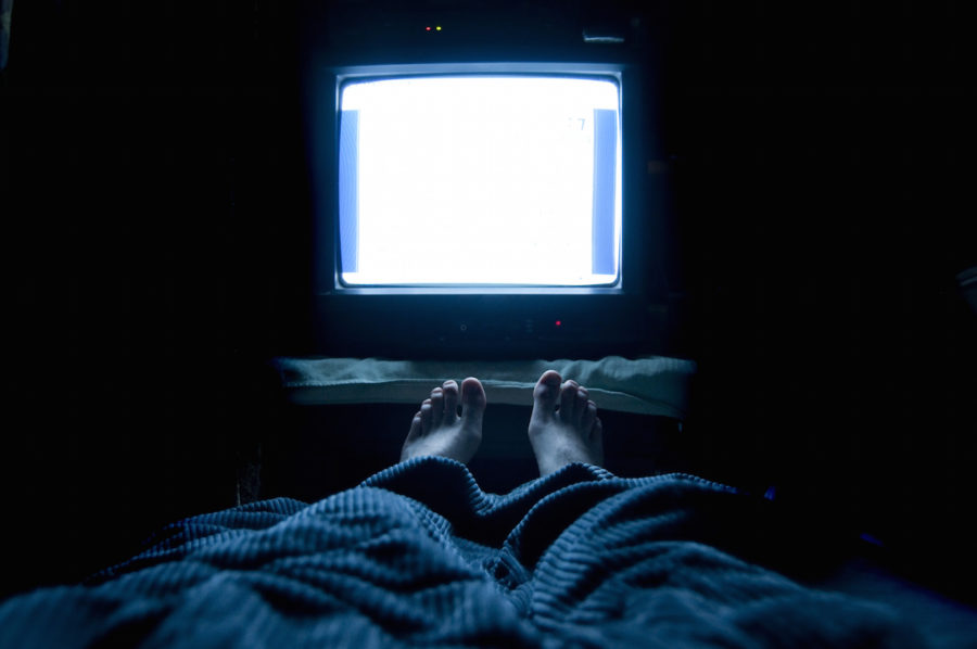 Person watches TV at night in his bed with his feet sticking up out of the blankets. The TV screen is blank white