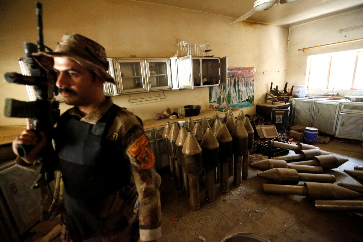 a-member-of-the-iraqi-counterterrorism-force-stands-by-an-isis-factory-in-fallujah