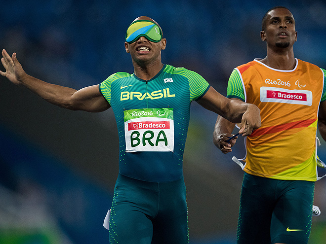 Felipe Gomes of Brazil with his guide Jonas de Lima Silva running the final leg of the men's 4x100m - T11-13 Round 1 Heat 1 in the Olympic Stadium during the Paralympic Games in Rio de Janeiro, Brazil on September 12, 2016. Handout photo by Bob Martin for OIS/IOC via AFP. RESTRICTED TO EDITORIAL USE. / AFP / IOS/OIC / Bob Martin for OIS (Photo credit should read BOB MARTIN FOR OIS/AFP/Getty Images)