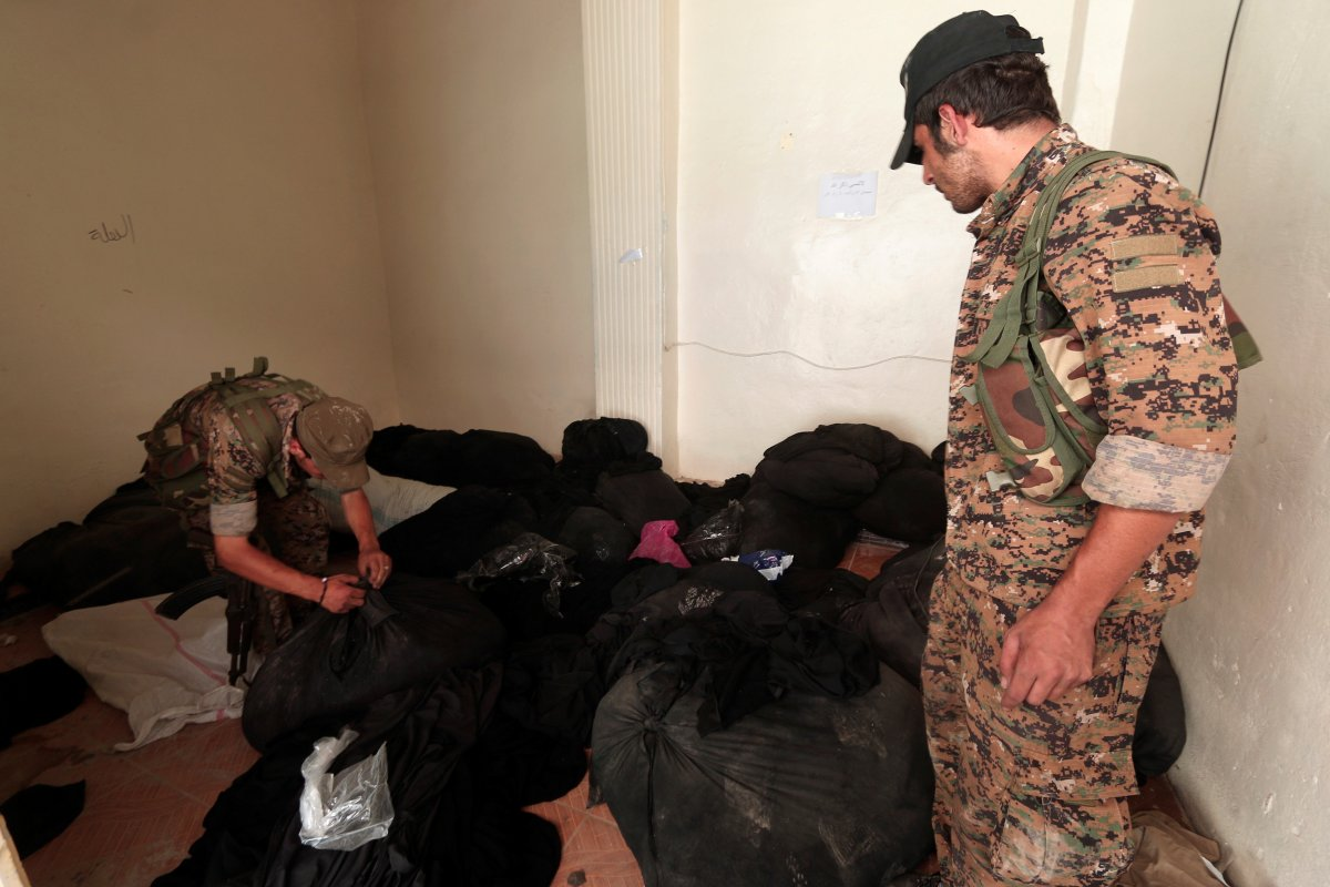 sdf-fighters-inspect-bags-of-niqabs-at-a-center-that-was-used-by-isis-religious-police-or-al-hisbah-in-manbij