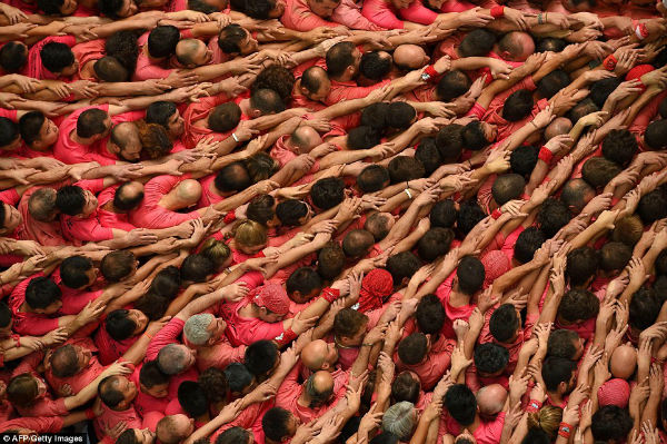 افراد گروه بازوهای خود را به یکدیگر قفل می کنند تا شالوده ای محکم برای برج انسانی شکل بگیرد