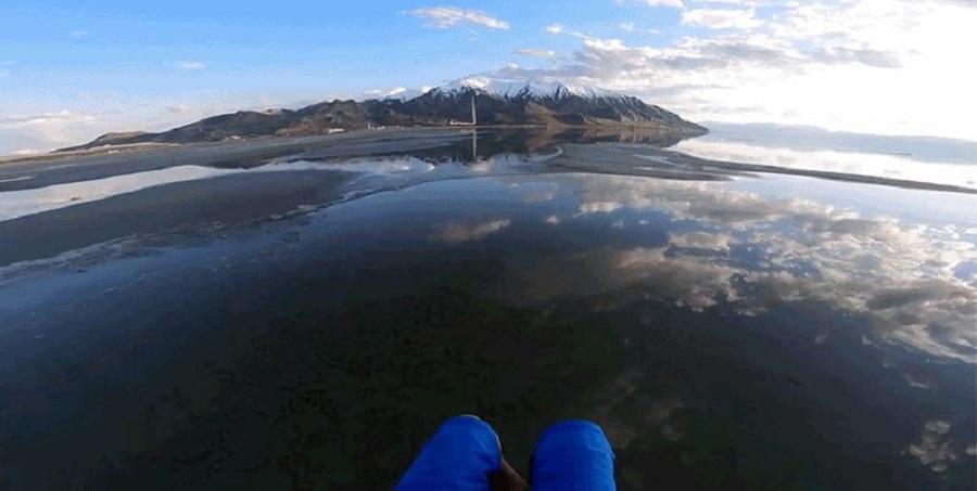 چتر سواری بر فراز دریاچه ای که همانند آینه بازتاب دهنده تصویر آسمان است [تماشا کنید]