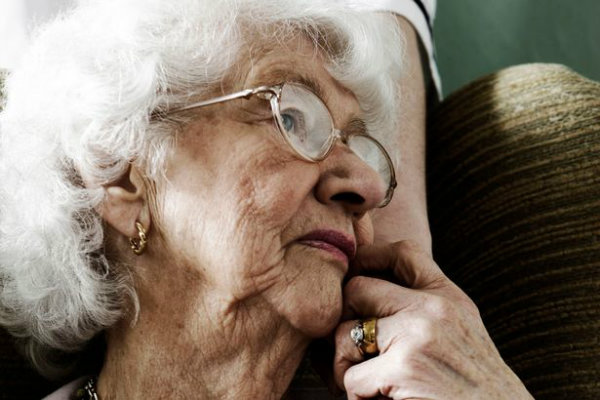 elderly-woman-sitting-in-chair-with-hand-of-care-worker-comforting-her-w600