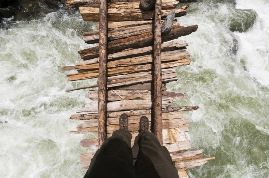 A point of view shot looking down of trekker crossing the swollen Kanka River on a rickety wodden bridge, Naranag, Gangabal Lake region, Kashmir Himalayas, India
