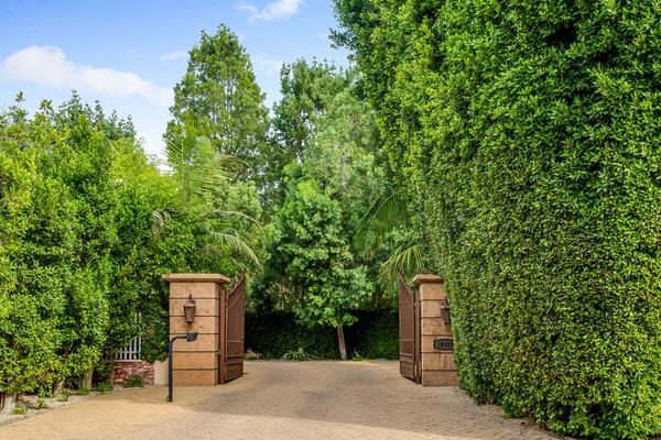 ورودی این خانه در میان انبوهی از درختان و گیاهان واقع شده است.