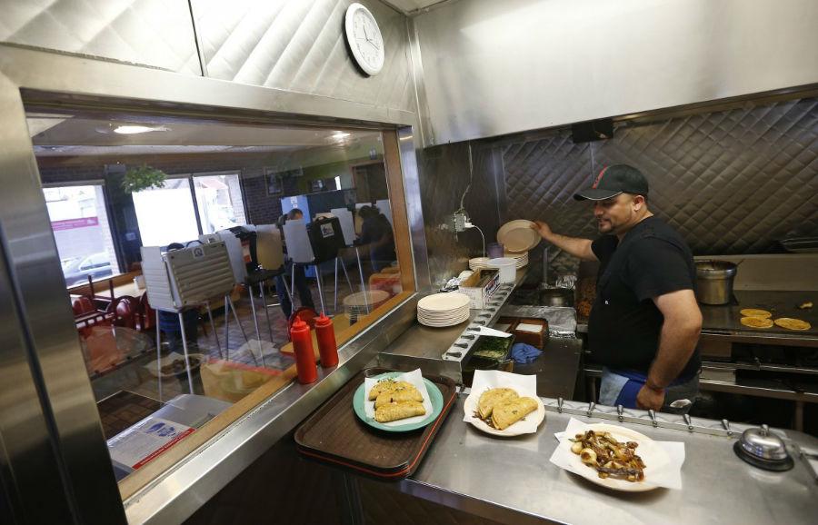 آشپزی در حال تهیه سفارش غذای مشتریانی است که برای دادن رای خود به این رستوران که به عنوان یکی از حوزه های رای گیری انتخاب شده، آمده اند. شیکاگو- ایلینویز