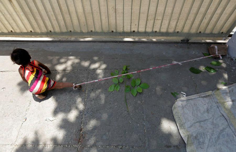 مادر این کودک 15 ماهه، طنابی به قوزک پای او بسته تا در زمانی که وی در حال کار در کارگاه ساختمانی است، این کودک از منطقه دور نشود. احمدآباد، هند - 19 آوریل
