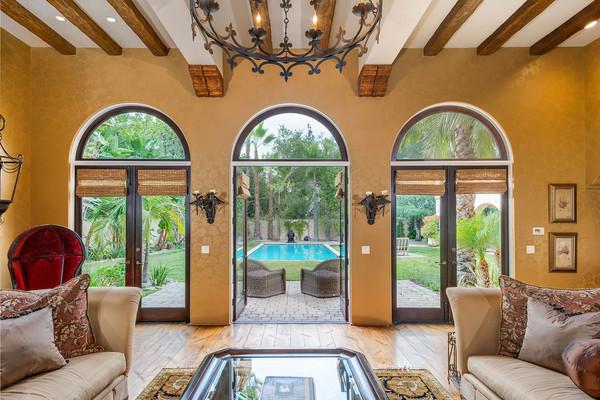 سه در بزرگ با طراحی قوسی شکل در فاصله بین حیاط و اتاق نشیمن، چشم انداز فوق العاده زیبایی درست کرده اند.