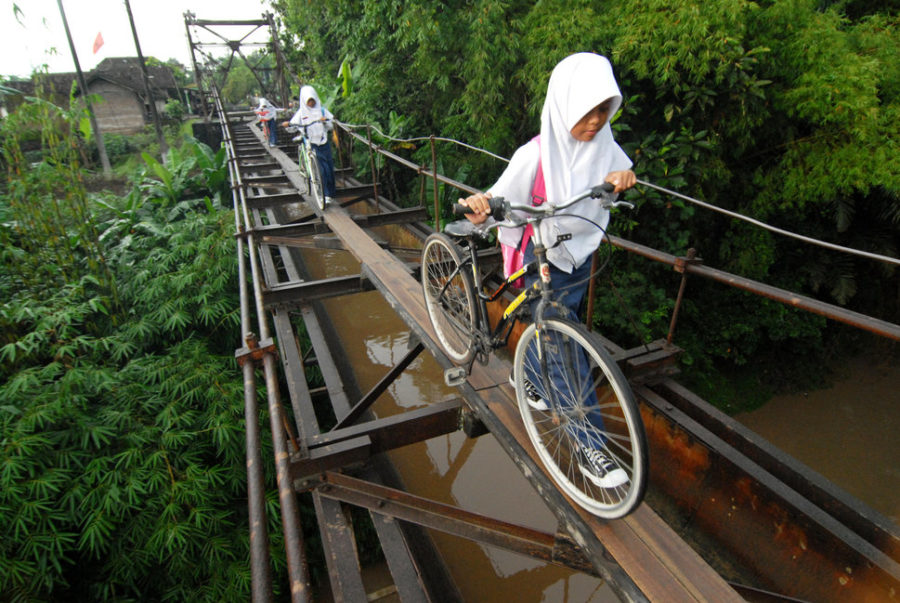 CENTRAL JAVA, INDONESIA - MARCH 11, 2014: Indonesian students go to school via suspension bridge that connects the Suro village and Plempungan village on March 10, 2014 in Boyolali, Central Java, Indonesia. The series of iron rods along the length of 30 meters and a width of 1.5 meters which is located 10 meters above the Pepe river is actually not a bridge, but the irrigation canals that drain water from the Cengklik reservoir to the surrounding rice fields. Built in the Dutch colonial period, people then use it as a bridge by adding sheets of wood over metal rods that ran above the water line. Students escape the danger while passing. (Photo by Agoes Rudianto/Anadolu Agency/Getty Images)