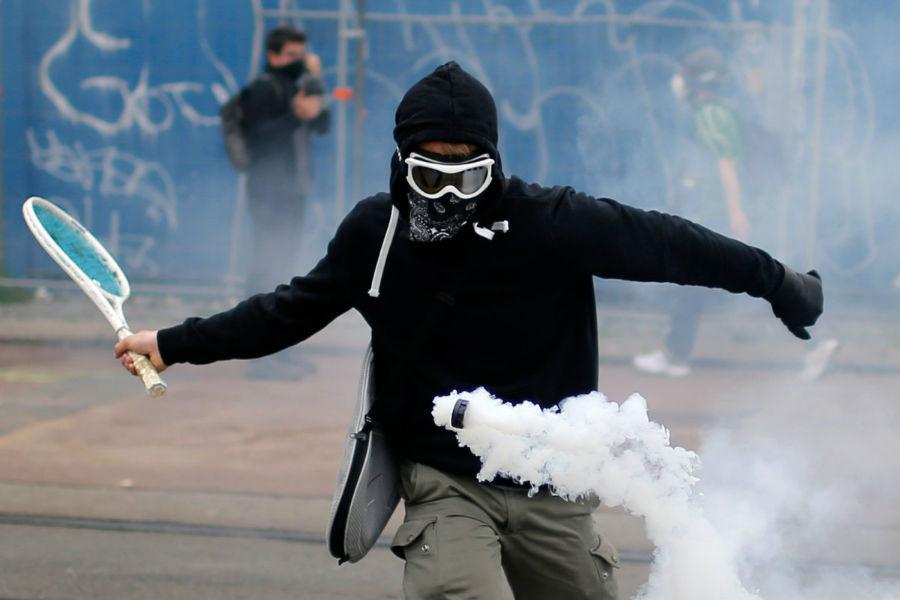 معترضی که در طول راهپیمائی های اعتراض آمیز به طرح قانون کار دولت، از راکت تنیس برای برگرداندن گازهای اشک آور استفاده می کند، فرانسه - 2 ژوئن