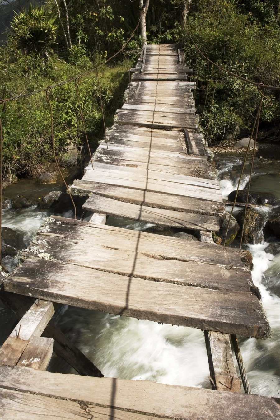 Bridge over the river Irubi. Old wooden bridge with missing parts.Valley of the river Irubi Imbabura Ecuador