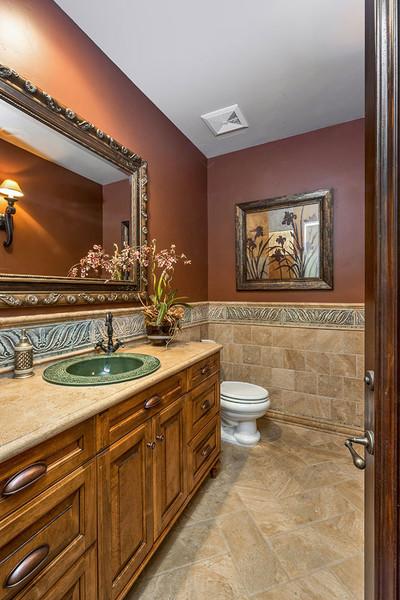 سرویس بهداشتی این خانه به رنگ قهوه ای است که با سنگ و چوب زینت کاری شده است.