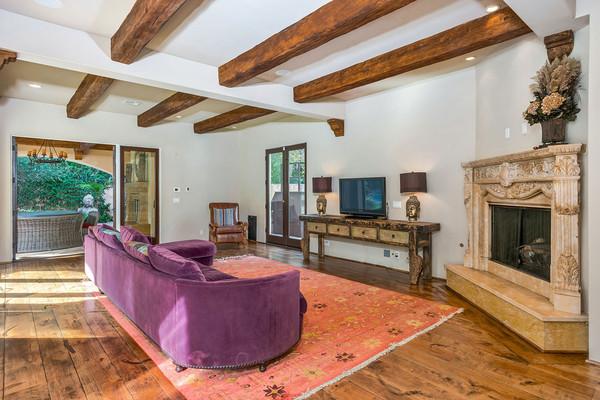کاناپه راحتی از جنس مخمل و به رنگ بنفش در کنار شومینه، فضایی راحت برای تماشای اخبار یا ویدئوهای موسیقی را تشکیل داده اند.