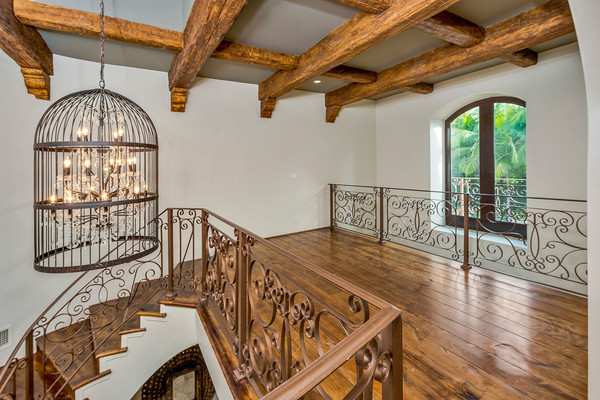 در بالای راه پله ها یک لوستر بزرگ به شکل قفس پرندگان، آویخته شده است.
