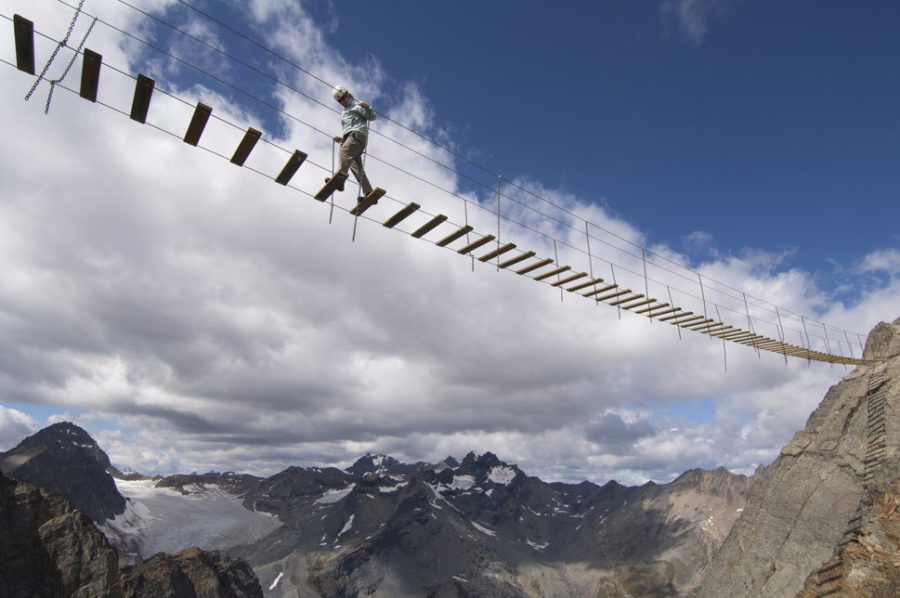 A woman crosses a bridge on a via ferrata in the Rocky Mountains in Canada. The via ferrata is on Mt. Nimbus, a peak only accissible via helicopter with Canadian Mountain Holidays.