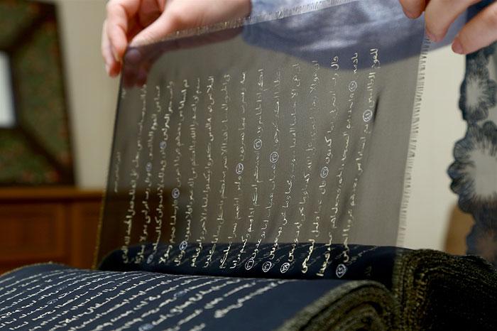 قرآنی که روی ۵۰ متر حریر و با جوهر طلا و نقره بازنویسی شده است