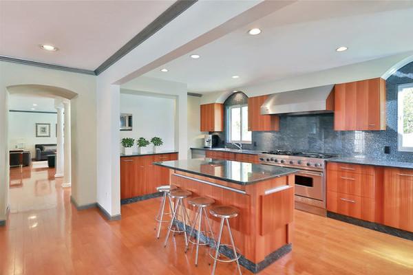 آشپزخانه این عمارت با رنگ های گرم طراحی شده و فضای باز زیادی را در اختیار کسی قرار می دهد که قصد دارد در آنجا آشپزی نماید.