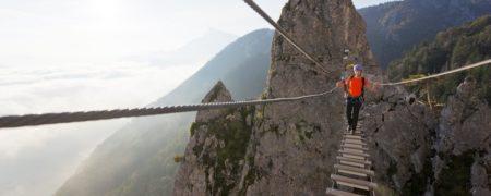Young woman crossing Dragon wall rope bridge
