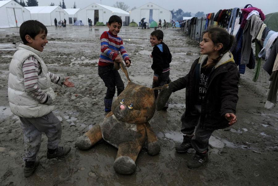 کودکان پناهنده ها در حال بازی با یک عروسک در کمپ پناهجویان در مرز یونان و مقدونیه - 15 مارس 2016