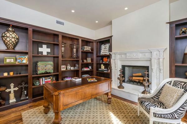 اتاق کار این خانه، یک فضای دنج و آرام است که به دلیل داشتن فرش، کتابخانه چوبی و شومینه هیزمی بسیار گرم و راحت به نظر می رسد.