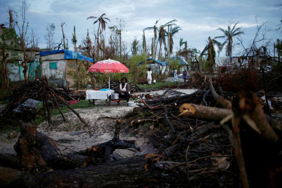 زن دست فروشی که پس از طوفان متیو در هایتی واقع در آمریکای جنوبی به فروش غذای گرم اقدام کرده و در انتظار مشتری است - 18 اکتبر