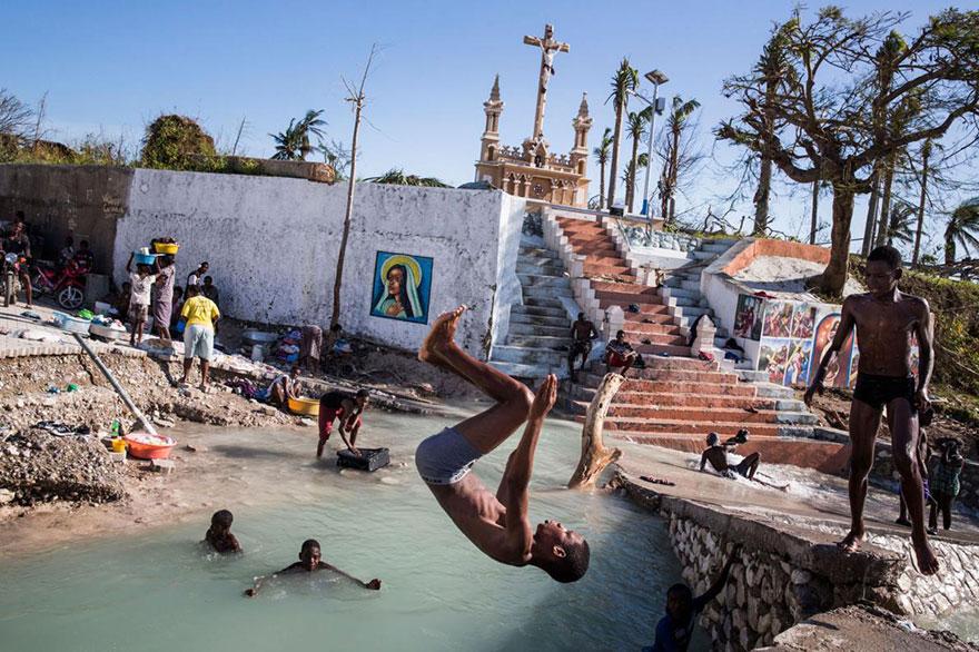 2- کودکان در حال شنا کردن در کنار پل شکسته رودخانه ای در پورت سلو در هایتی هستند. این شهر در نتیجه توفان متیو آسیب جدی دیده و تقریبا تمامی ساختمان های آن از بین رفته اند.