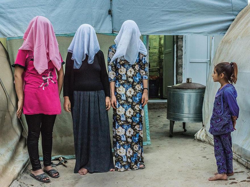 24- دخترک در حال تماشای سه زن کرد است که صورت خود را با روسری هایشان پوشانده اند. آنها بیان داشته اند که پیش از فرار و پناه بردن به چادر پناهندگان، نیروهای داعش آنها را مجبور به ازدواج کرده بوده اند.