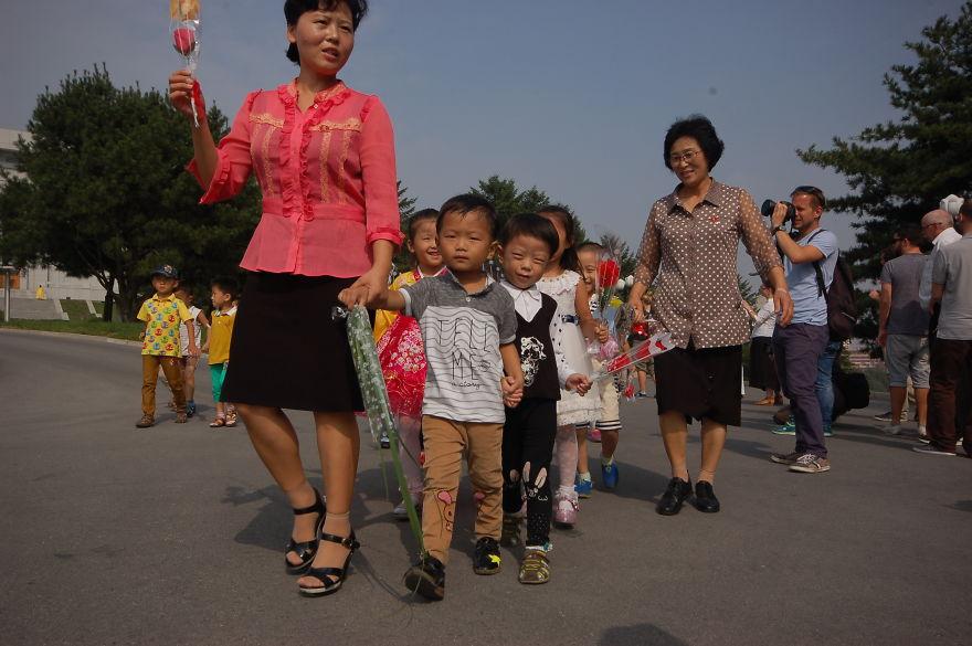کودکانی که با گل در مسیر ادای احترام به کیم ایر سانگ و کیم جونگ ایل هستند.