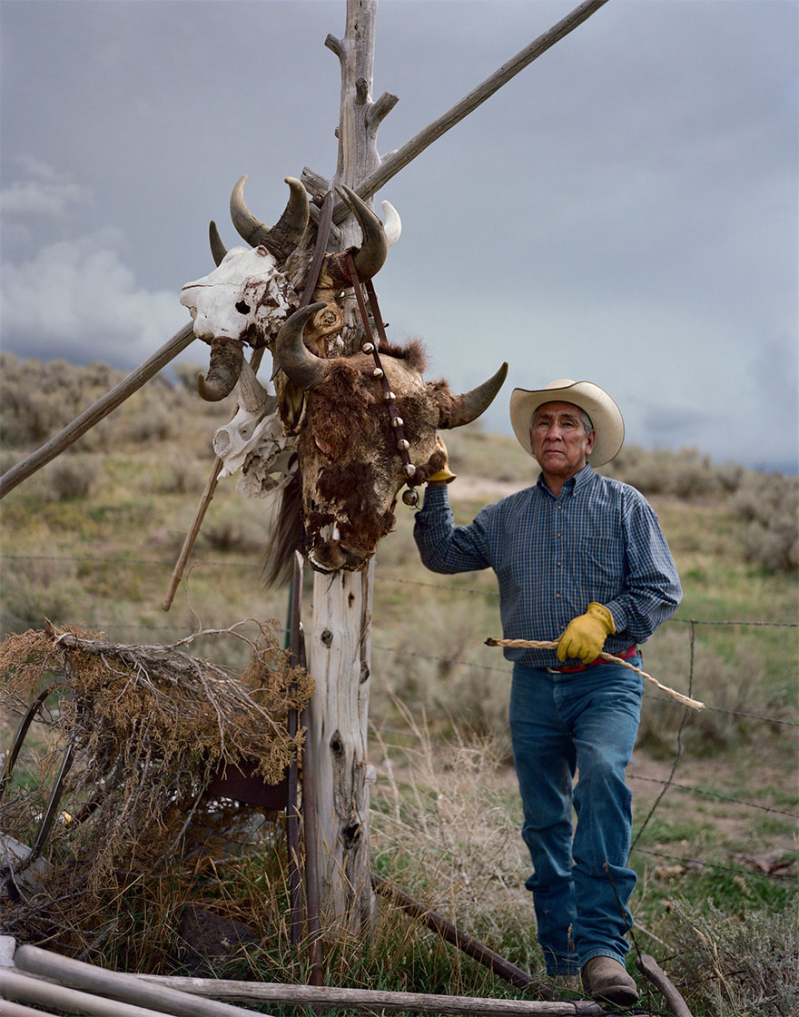 3- «لئو تتون» در فورت هال ایالت آیداهو، در کنار تیرکی که اسکلت های جمجمه گاو وحشی آمریکائی از آن آویخته شده، ایستاده است. این تصویر نشان دهنده ارتباط معنوی اهالی قبیله شوشونه و گاوهای وحشی (بایسون) است.