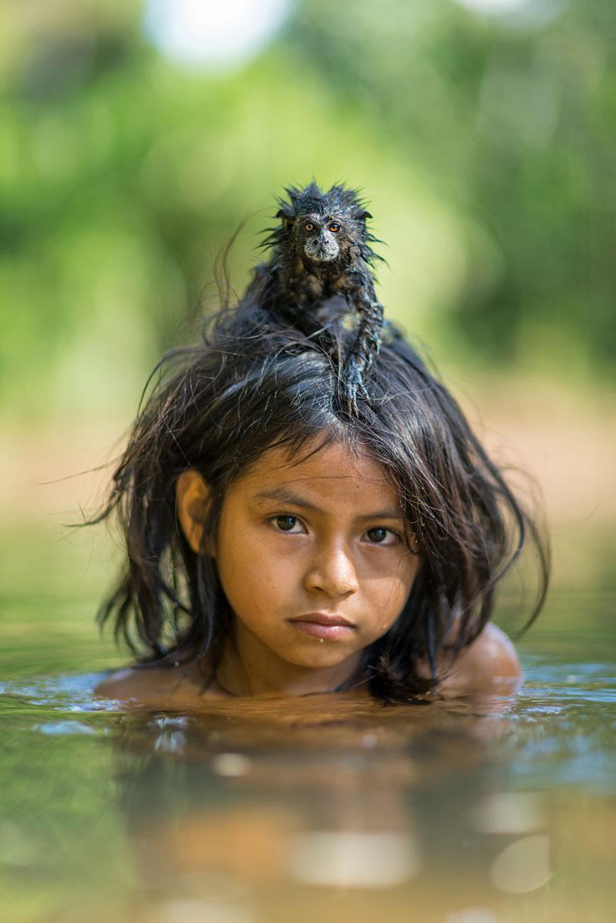 48- یک تامارین (بومی آمریکای جنوبی) روی سر دخترکی به نام «یوینا مامریا» نشسته است که درون رودخانه Yomibato مشغول بازی است. این رودخانه در پارک ملی Manú پرو واقع شده است.