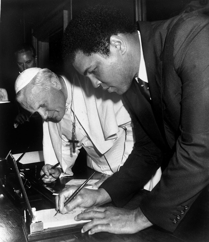 محمدعلی در حال امضا کردن در واتیکان سیتی در حضور پاپ جان پاول دوم