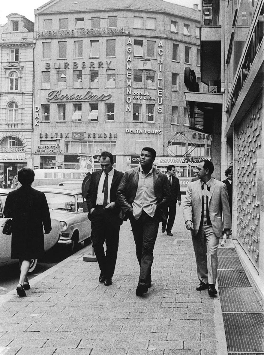 کلی در حال پیاده روی در یکی از خیابان های اصلی شهر فرانکفورت در آلمان در حالی که یک روزنامه نگار قصد مصاحبه کردن با او را دارد - 1966