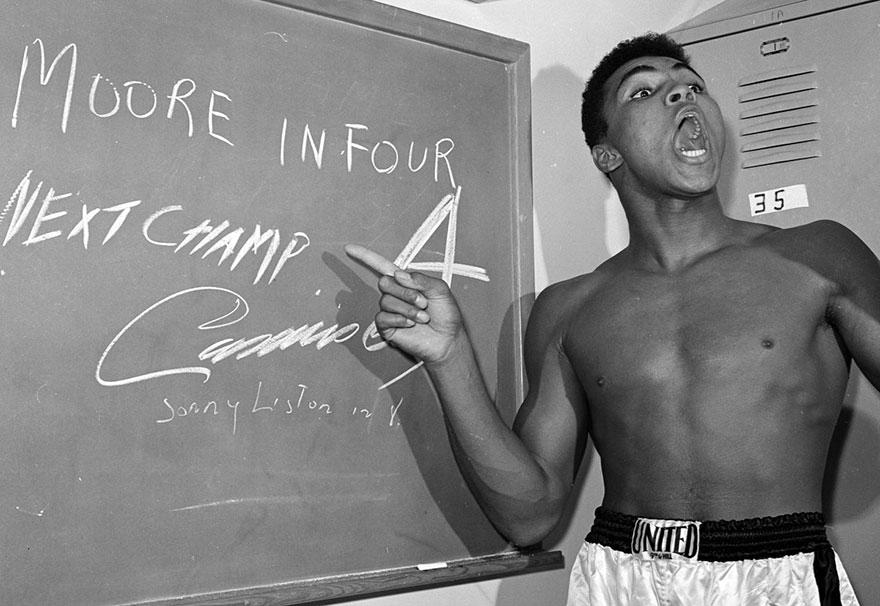 محمدعلی جوان به امضایی که روی تخته در اتاق تعویض لباس کشیده اشاره می کند. این عکس به پیش از مسابقه او با آرچی مور در لس آنجلس تعلق دارد.