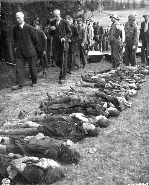 غیرنظامی های آلمانی در حال عبور اجباری از کنار جنازه های کشته شده گان هولوکاست در ماه می سال 1945