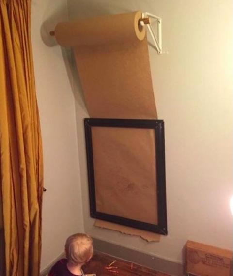 2- برای اینکه فرزند شما روی همه دیوارهای خانه با خودکار و مداد رنگی، نقش و نگار نکشد، یک رول بزرگ کاغذ بخرید و آن را روی دیوار نصب کنید. در قسمت پایین دیوار که هم قد فرزند شماست، یک قاب خالی نصب کرده و کاغذ را از زیر آن عبور دهید تا کودک درون آن قاب شاهکارهای رنگی خودش را ترسیم کند.