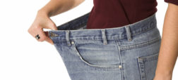 Female showing how much weight she has lost by wearing her old jeans that are sizes too big