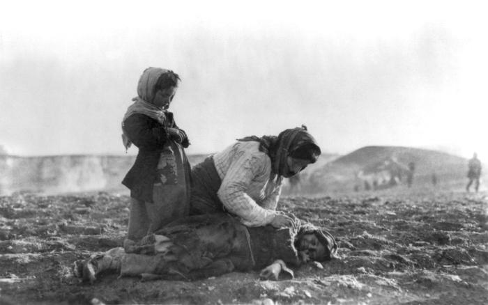 Armenian_woman_kneeling_beside_dead_child_in_field-w700