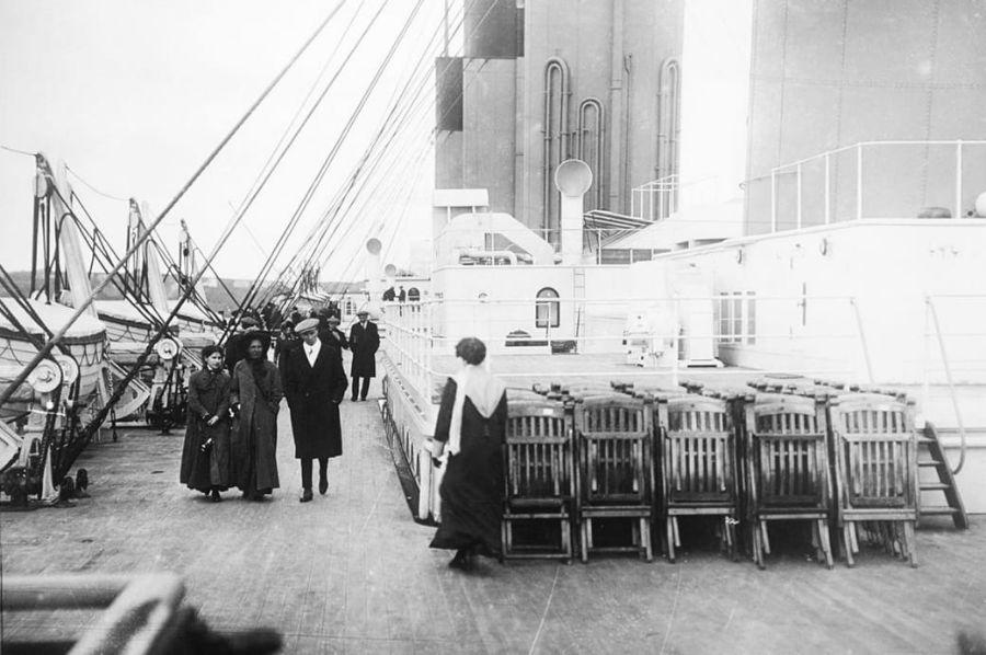 مسافران در حال عبور از کنار صندلی های چیده شده روی عرشه کشتی هستند.