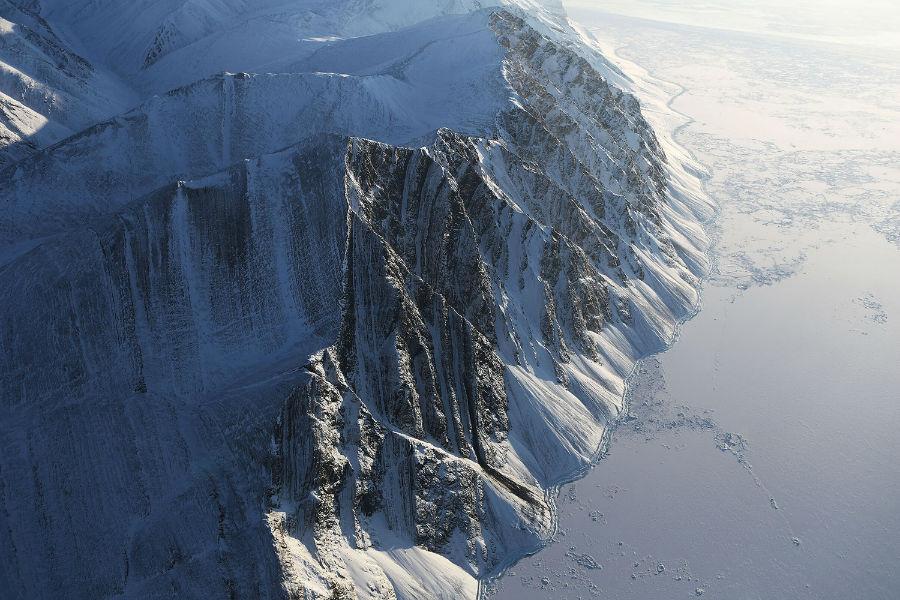 چشم اندازی از یخچال طبیعی که از داخل هواپیمای تیم تحقیقاتی ماموریت آیسبرگ ناسا در تاریخ 29 مارس سال 2017 از بالای جزیره السمر در کانادا گرفته شده است. زمین های یخی جزیره Ellesmere به دلیل گرم شدن هوا در حال عقب نشینی هستند.