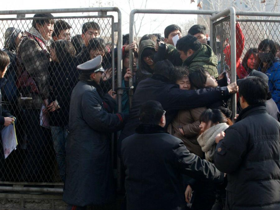 پلیس در حال مهار کردن افرادی است که برای ثبت نام در امتحان ورودی در جلوی درب ازدحام کرده اند.