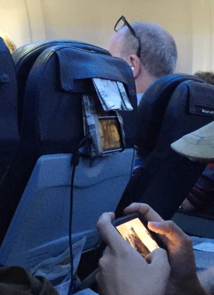 در این تصویر، نبوغ مسافری را می بینید که روزنامه را تا و از آن به عنوان نگهدارنده موبایل استفاده کرده است.