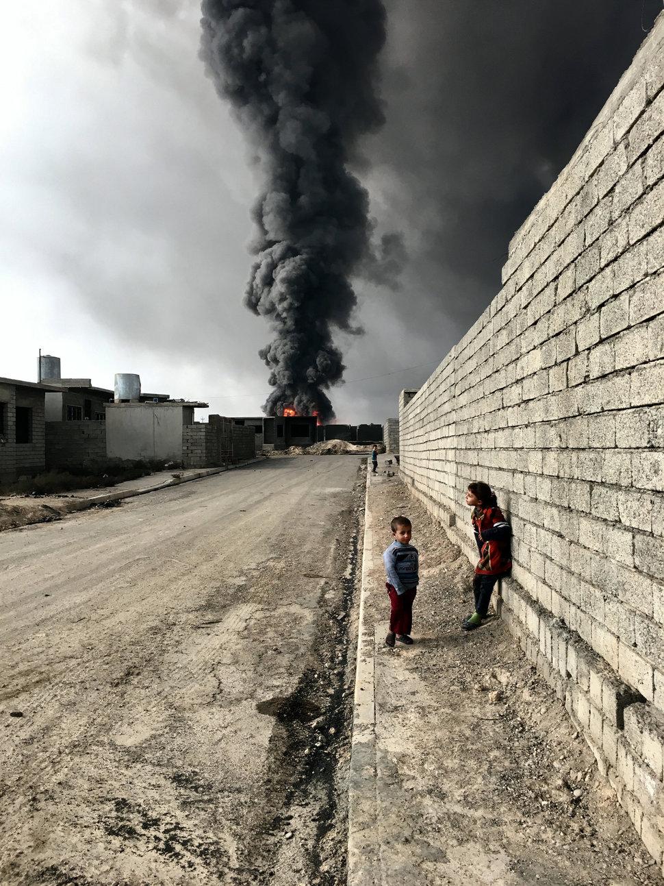 کودکانی که در کنار دیوار در نزدیکی دود و آتشی که نیروهای داعش برپا کرده اند، ایستاده اند.