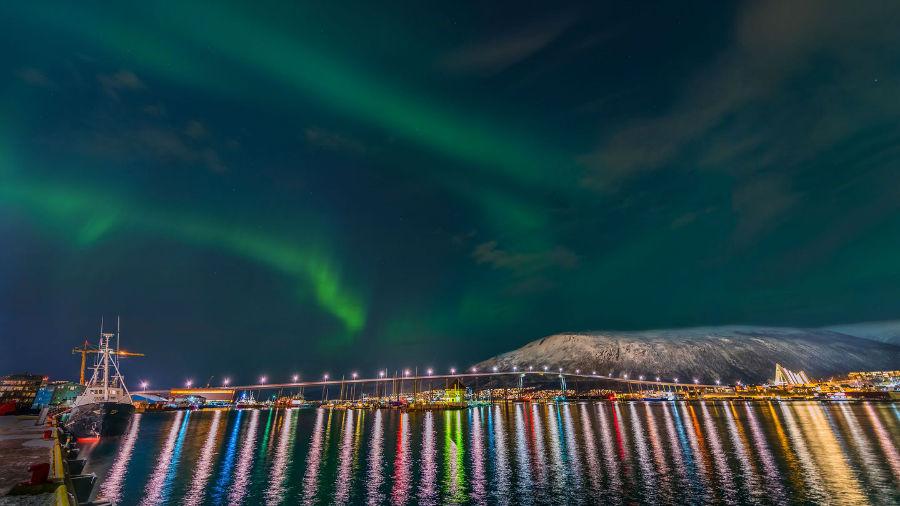 شفق شمالی بر فراز نورهای رنگی که در آب تابیده و منظره زیبایی را تشکیل داده اند.