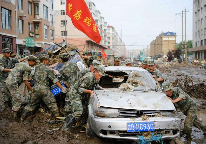 نیروهای امداد در حال جا به جا نمودن خودرویی هستند که در نتیجه جاری شدن سیل عظیمی در یونگجی در استان جیلیلن در کشور چین، در گِل و لای گیر کرده است. 17 جولای (26 تیر)