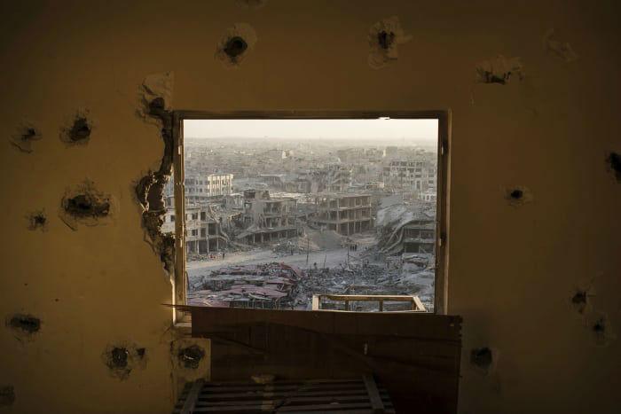 چشم اندازی از خرابی های شهر موصل از قاب پنجره ساختمانی تخریب شده در این شهر در روز 11 جولای (20 تیر). پلیس عراق موفق شد پس از حدود 9 ماه جنگ، شهر موصل را از چنگ نیروهای داعش آزاد سازد.
