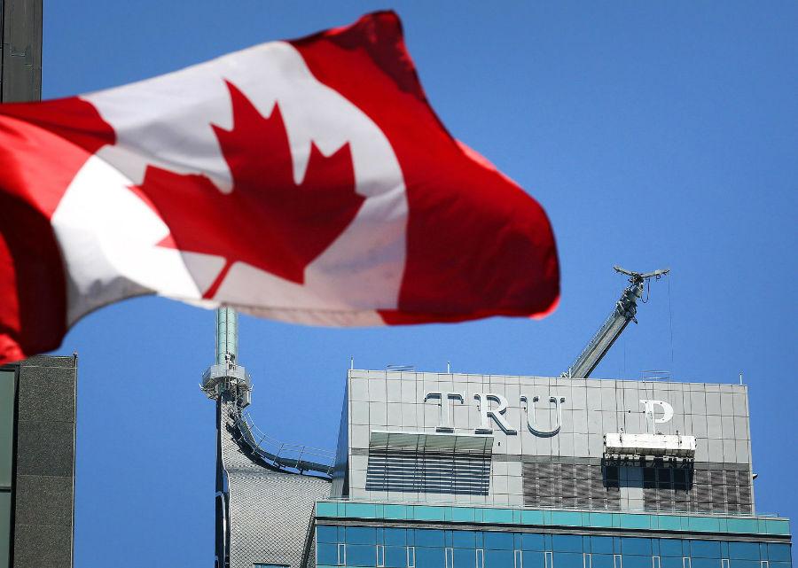 کارگران در حال حذف حروفِ واژه ی TRUMP از سر در هتل و برج بین المللی ترامپ در مرکز شهر تورنتو در روز 18 جولای (27 تیر) هستند. مالک جدید این ساختمان، JCF Capital ULC که در ماه گذشته میلادی این بنا را از مجموعه هتل های ترامپ خریداری نمود.
